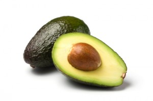 whole and half avocado isolated on white